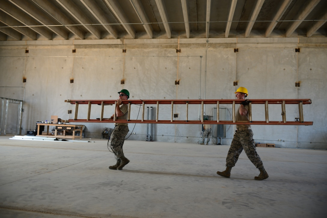 From the left, U.S. Air Force Tech. Sgt. Donald Linscott and Staff Sgt. Ben Keeler, both assigned to the 157th Civil Engineering Squadron, New Hampshire Air National Guard, carry a ladder during construction on the Commando Warrior Training Facility, Andersen Air Force Base, Guam, June 20, 2016. 157 CES Airmen are deployed to Guam for annual training where they are working on a construction project for the Pacific Command Regional Training Center. (Air National Guard photo by Airman 1st Class Ashlyn J. Correia)