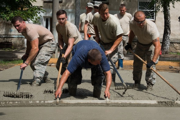 U.S. Airmen, assigned to the 185th Civil Engineering Squadron, Iowa Air National Guard, participate in the construction of a basketball court as part of a Humanitarian Civil Assistance (HCA) project in Chisinau, Moldova, June 22, 2016. As part of the European Command's (EUCOM) Humanitarian and Civic Assistance Program, the 123rd Civil Engineering Squadron from the Kentucky Air National Guard, 185th Engineering Squadron from the Iowa Air National Guard, 457th Civil Affairs Battalion and Moldovan Land Forces collaborate to renovate to the kitchen at Special School Number 12 for Hearing Impaired Children, in Chisinau, Moldova, June 3-25, 2016. (U.S. Army Photo by Pfc. Emily Houdershieldt/released)