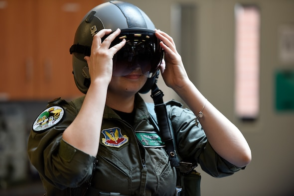 Honorary 2nd Lt. Ashleigh Hunt tries on a pilot's helmet May 26, 2016 during Pilot for a Day at the 180th Fighter Wing in Swanton, Ohio. Pilot for a Day, a program supporting children and young adults who live with chronic or life-threatening illnesses, allows the 180FW to give back to the local community, whose enduring support for the Airmen makes the 180FW mission possible. (U.S. Air National Guard photo by Staff Sgt. Shane Hughes)