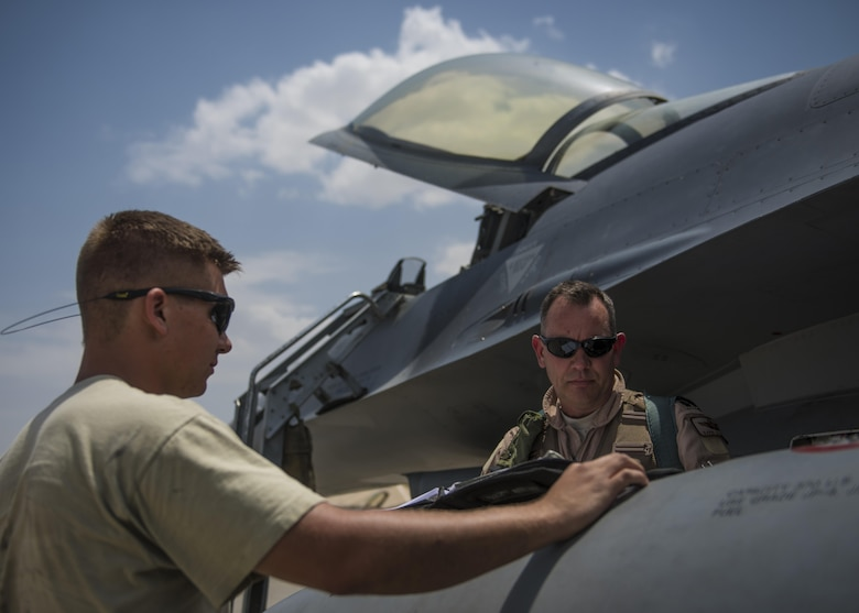 Lt. Col. David Efferson (right), 457th Expeditionary Fighter Squadron commander, and Senior Airman Brandon Hellin (left), 455th Expeditionary Maintenance Squadron crew chief, review an F-16C Fighting Falcon flight checklist, June 28, 2016, Bagram Airfield, Afghanistan. The F-16C is a compact, multi-role fighter aircraft that is highly maneuverable in air-to-air combat and air-to-surface attacks. (U.S. Air Force photo by Senior Airman Justyn M. Freeman)