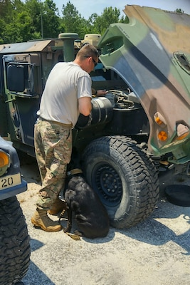 U.S. Army Staff Sgt. Michael Hutcheson, 133rd Military Police Company, South Carolina Army National Guard, works on his military vehicle while his service dog Samantha stands by for support to assist him combat certain Post Traumatic Stress Disorder symptoms while at drill in Timmonsville, S.C., June 25, 2016. Hutcheson has been battling PTSD as a result of multiple combat deployments in support of both Operation Iraqi Freedom and Operation Enduring Freedom.