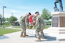 """Command Sgt. Maj. Joseph Cornelison, 1st Infantry Division senior noncommissioned officer, and Maj. Gen. Wayne W. Grigsby Jr., commanding general of the 1st Inf. Div. and Fort Riley, lay a wreath at the Fallen Soldier Memorial on June 8 in Victory Park at Fort Riley. The ceremony is held each year in honor of fallen """"Big Red One"""" Soldiers."""