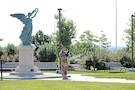 Chief Warrant Officer 3 Jeffrey Price, 1st Infantry Division, plays the bagpipes during the wreath-laying ceremony June 8 in Victory Park. The cere¬mony served as a reminder of the 1st Inf. Div. lives lost in combat since the beginning of the Global War on Terrorism.