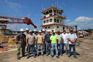 The Tulsa District U.S. Army Corps of Engineers navigation maintenance vessel Captain and crew stand in front of their boat, Mr. Pat, near Sallisaw, Oklahoma, June 15, 2016. Mr. Pat was christened and put into service at the District on June 28, 1996, and for the past 20 years has been instrumental in the facilitation of maintenance along the Tulsa District's portion of the McClellan-Kerr Arkansas River Navigation System. (U.S. Army Corps of Engineers photo by Preston Chasteen/Released)