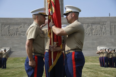 Major Alfred L. Butler IV, outgoing Marine Corps Recruiting Station Kansas City commanding officer, prepares to pass the recruiting station's unit colors to Maj. Byron R. Johnson, incoming recruiting station commanding officer, during the RS's change-of-command ceremony at the Liberty Memorial, June 23, 2016. The passing of the unit colors represents the formal passing of responsibility of one commanding officer to another and ensures a unit is never without official leadership.