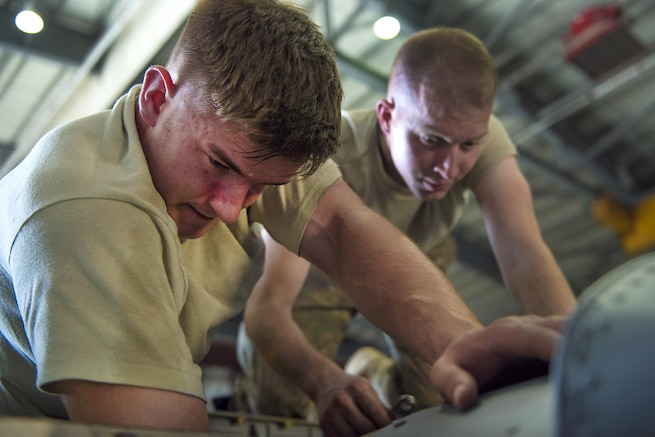 Air Force Senior Airmen Brady Thompson, left, and William Willmann replace a fire overheat protection system in a C-130J Super Hercules aircraft engine at Bagram Airfield, Afghanistan, June 27, 2016. Air Force photo by Senior Airman Justyn M. Freeman