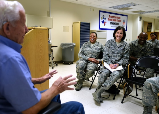 Retired Tech. Sgt. Arnold Parker (left), a Korean War veteran who worked in nutritional medicine on Lackland Air Force Base, Texas, in the early 1950s, speaks with members of the 59th Diagnostics and Therapeutics Squadron during a session of the Deliberate Development Program June 20 at the Armed Services Blood Bank Center, Joint Base San Antonio-Lackland, Texas. The program develops Airmen of all ranks in areas, which include leadership, management and self-improvement. It encourages networking and access to other members of the medical team. (U.S. Air Force photo/Staff Sgt. Kevin Iinuma)