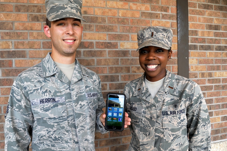 U.S. Air Force Staff Sgt. Charles Herron, 17th Medical Support Squadron command support staff NCO in charge, and 2nd Lt. Mara Hood, 17th MDSS group practice manager, pose for a photo with the new 17th Medical Group app outside the Ross Clinic on Goodfellow Air Force Base, Texas, June 24, 2016. The app is set to release in July on a variety of platforms and assist individuals with their healthcare information needs.
