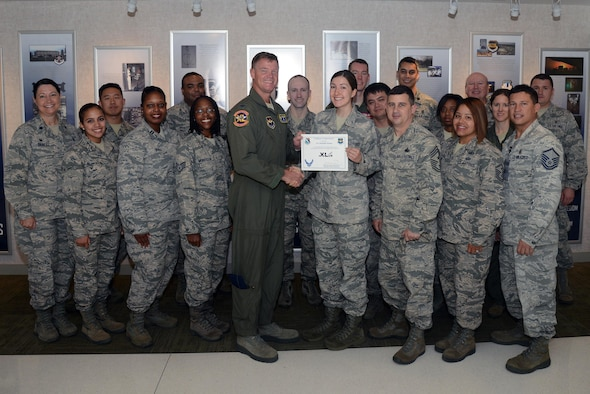 "Senior Airman Danielle Dooms, 47th Medical Operations Squadron health technician, accepts the ""XLer of the Week"" award from Col. Thomas Shank, left, 47th Flying Training Wing commander, and Chief Master Sgt. George Richey, 47th FTW command chief, here, June 22, 2016. The XLer is a weekly award chosen by wing leadership and is presented to those who consistently make outstanding contributions to their unit and Laughlin. (U.S. Air Force photo/Airman 1st Class Brandon May)"