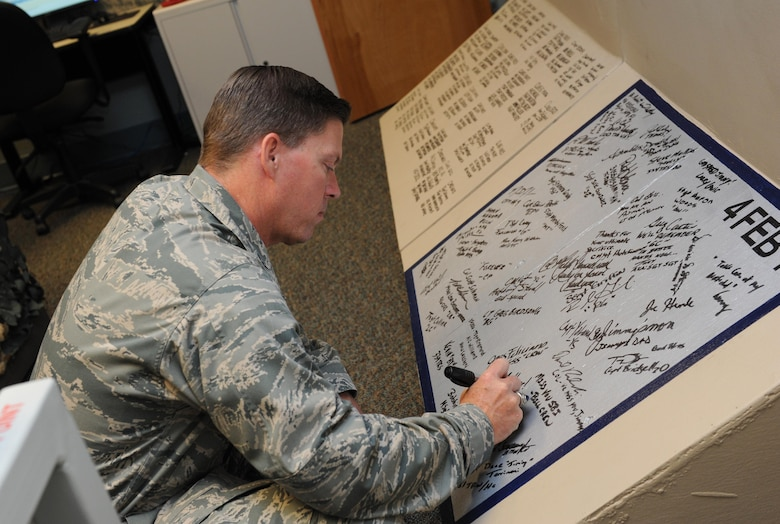 """Col. C. Mike Smith, 81st Training Wing vice commander, signs a """"T-wall"""" inside the Hansen Room at Cody Hall during an 81st Training Group immersion tour June 22, 2016 on Keesler Air Force Base, Miss. The purpose of the tour was to become familiar with the group's mission, operations and personnel. (U.S. Air Force photo by Kemberly Groue/Released)"""