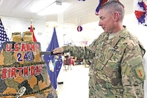 "Command Sgt. Maj. Larry Orvis, senior noncommissioned officer of the 2nd Armored Brigade Combat Team, 1st Infantry Division, cuts the ceremonial Army birthday cake June 14 at the Camp Buehring, Kuwait, dining facility. Soldiers of the ""Dagger"" brigade celebrated the Army's 241st birthday with a run and cake cutting."