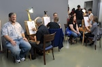 Employees and family members sit for their caricatures at the 2016 HQC Family Day at the McNamara Headquarters Complex at Fort Belvoir, Virginia, June 28.