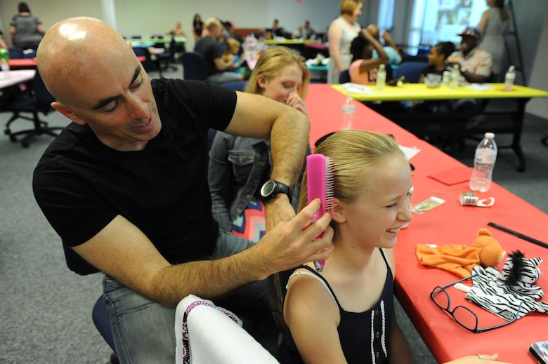 "Retired Maj. Lamar Settlemires, brushes his daughter Elena's hair during a Daddy/Daughter Dinner and a ""Do"" event at the Sablich Center June 24, 2016 on Keesler Air Force Base, Miss. The event included dinner and hands-on hair styling techniques for the dads, which provided a valuable opportunity for sharing, learning new practical skills and deepening the bond between the dads and their daughters. (U.S. Air Force photo by Kemberly Groue/Released)"