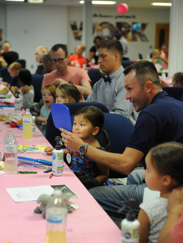"Tech. Sgt. Blaine Caudill, 81st Operations Support Flight air traffic controller assistant chief, holds a mirror for his daughter, Mia, as she inspects her hair during a Daddy/Daughter Dinner and a ""Do"" event at the Sablich Center June 24, 2016 on Keesler Air Force Base, Miss. The event included dinner and hands-on hair styling techniques for the dads, which provided a valuable opportunity for sharing, learning new practical skills and deepening the bond between the dads and their daughters. (U.S. Air Force photo by Kemberly Groue/Released)"