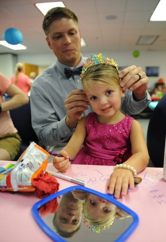 "Second Lt. David Giannotti, 81st Logistics Readiness Squadron distribution officer in charge, places a tiara on his daughter, Paisley during a Daddy/Daughter Dinner and a ""Do"" event at the Sablich Center June 24, 2016 on Keesler Air Force Base, Miss. The event included dinner and hands-on hair styling techniques for the dads, which provided a valuable opportunity for sharing, learning new practical skills and deepening the bond between the dads and their daughters. (U.S. Air Force photo by Kemberly Groue/Released)"