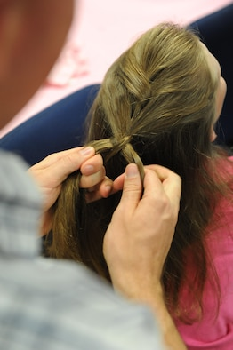"Staff Sgt. Garrett Lethco, 335th Training Squadron instructor, attempts to French braid his daughter, Taylor's hair during a Daddy/Daughter Dinner and a ""Do"" event at the Sablich Center June 24, 2016 on Keesler Air Force Base, Miss. The event included dinner and hands-on hair styling techniques for the dads, which provided a valuable opportunity for sharing, learning new practical skills and deepening the bond between the dads and their daughters. (U.S. Air Force photo by Kemberly Groue/Released)"