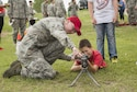 A security forces Airman shows a Minot child how to hold and aim an unloaded gun during Heroes in Training at Minot Air Force Base, N.D., June 24, 2016. Heroes in Training showcased displays from the fire department, security forces, medical group and other first responding base agencies. (U.S. Air Force photo/Airman 1st Class Christian Sullivan)