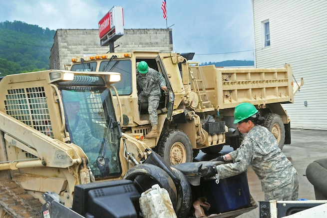 Soldiers help remove debris after severe flooding in Rainelle, W.Va., June 27, 2016. The soldiers, assigned to the Rhode Island Army National Guard's 861st Engineer Company, stayed in West Virginia after their annual training to assist with cleanup efforts. Army National Guard photo by Staff Sgt. Justin Hough