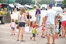 Kids play at a vendors' station, chasing bubbles, at the Manhattan, Kansas, Downtown Farmers' Market. Activities can be found for children at the market and surrounding businesses downtown on Saturday mornings.