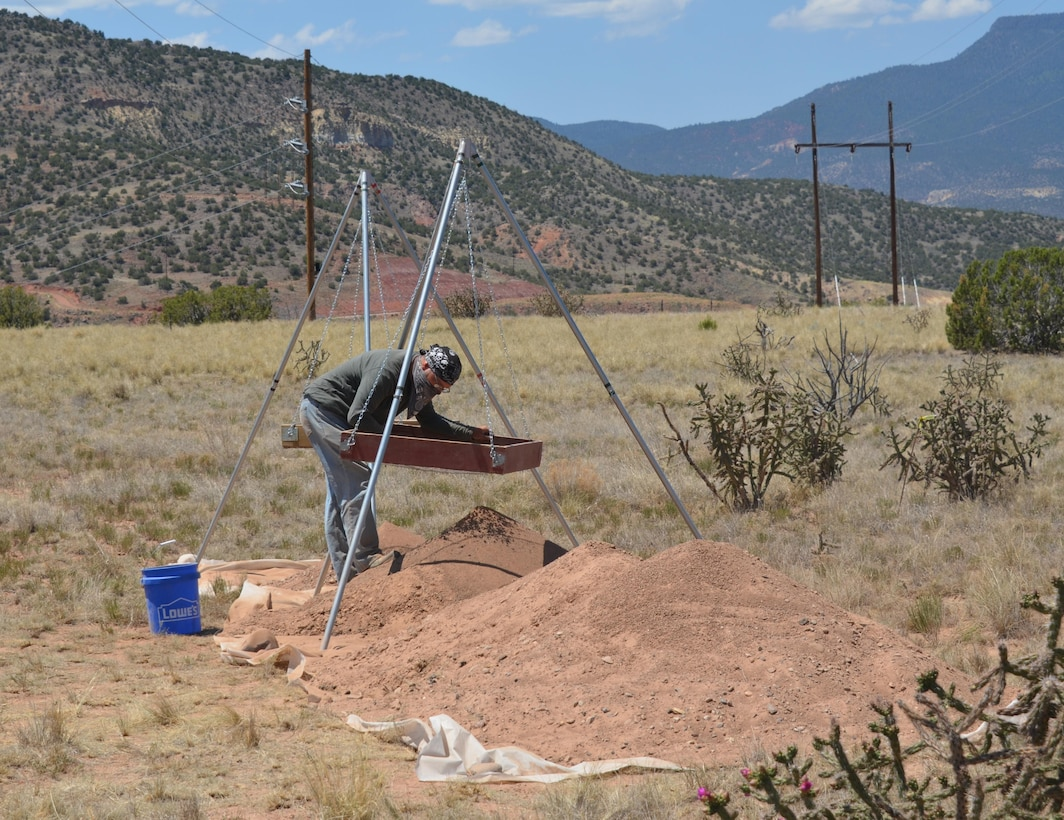 ABIQUIU LAKE, N.M. – Undergraduate student Ray Frazier screens dirt from the site looking for artifacts, June 21, 2016.