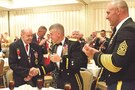 """Maj. Gen. Wayne W. Grigsby Jr., 1st Infantry Division and Fort Riley commanding general, shakes hands with Ray Lambert, a """"Big Red One"""" veteran from World War II, on June 11 at the Society of the 1st Infantry Division reunion in Atlanta. Grigsby and Command Sgt. Maj. Joseph Cornelison, right, the division's senior noncommissioned officer, met with several World War II veterans at the reunion, including Lambert, who served as a medic with the 16th Infantry Regiment during the D-Day invasion."""
