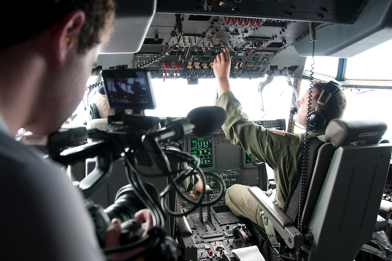"Thom Patterson, CNN videographer (left), uses a camera to capture footage of 53d Weather Reconnaissance Squadron ""Hurricane Hunter"" pilots inside the cockpit of a C-130 Hercules during a flight over Maryland June 28, 2016. As part of the 100th anniversary of air power in the U.S. military, members of the media were invited to fly with the Hurricane Hunters and learn about their weather surveillance mission. With ten deployable C-130s, the unit has the only routine aerial weather reconnaissance mission in the world. (U.S. Air Force photo/Staff Sgt. Kat Justen)"