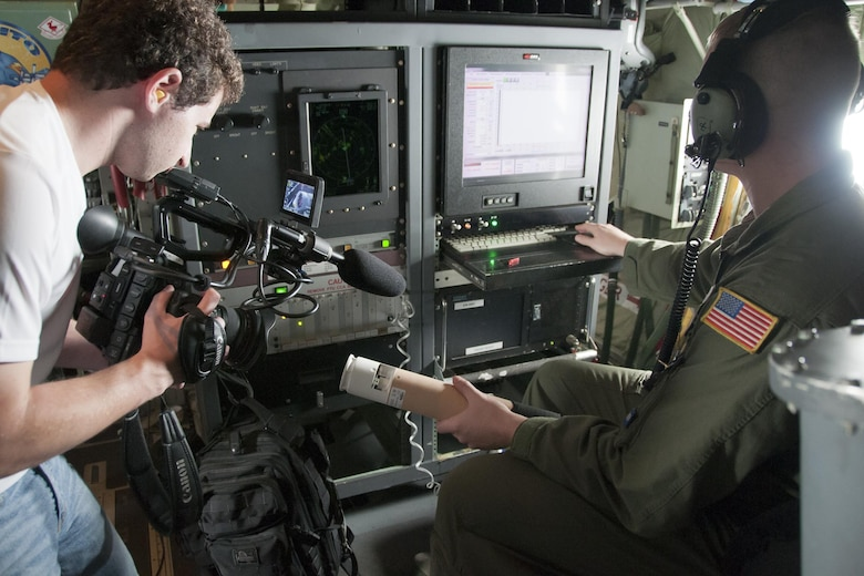Thom Patterson, CNN videographer (left), uses a camera to capture footage of a dropsonde inside a 53d Weather Reconnaissance Squadron Hurricane Hunters C-130 Hercules during a flight over Maryland June 28, 2016. A dropsonde is used by the Hurricane Hunters to collect temperature, humidity, wind speed and direction of weather systems. The information is then sent to the National Hurricane Center in Miami to monitor tropical storms. As part of the 100th anniversary of air power in the U.S. military, members of the media were invited to fly with the Hurricane Hunters and learn about their weather surveillance mission. With ten deployable C-130s, the unit has the only routine aerial weather reconnaissance mission in the world. (U.S. Air Force photo/Staff Sgt. Kat Justen)