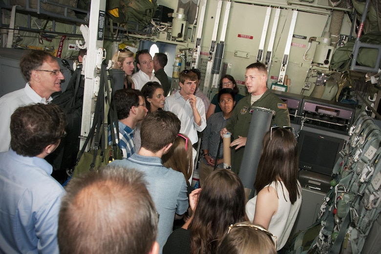 "Staff Sgt. Jesse Jordan, 53d Weather Reconnaissance Squadron ""Hurricane Hunters"" loadmaster, discusses the use and function of a dropsonde tube to a group of congressional staffers inside a C-130 Hercules on the Joint Base Andrews, Md., flight line June 29, 2016. A dropsonde tube is used by the Hurricane Hunters to collect temperature, humidity, wind speed and direction of weather systems. The information is then sent to the National Hurricane Center in Miami to monitor tropical storms. As part of the 100th anniversary of air power in the U.S. military, members of the media were invited to fly with the Hurricane Hunters and learn about their weather surveillance mission. With ten deployable C-130s, the unit has the only routine aerial weather reconnaissance mission in the world. (U.S. Air Force photo/Staff Sgt. Kat Justen)"