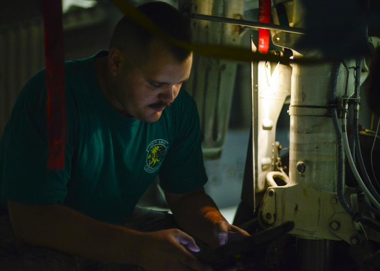 Senior Airman Jarred Sozzi, 25th Aircraft Maintenance Unit electronic and environmental systems technician, reads through a technical order while placing a weight-on-wheel harness and switch on an A-10 Thunderbolt II at Osan Air Base, Republic of Korea, June 24, 2016. Sozzi grew up admiring the A-10 before joining the Air Force, ultimately choosing to perform maintenance on his favorite aircraft for a living. (U.S. Air Force photo by Senior Airman Victor J. Caputo/Released)