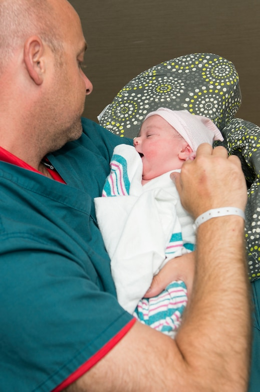 U.S. Air Force Master Sgt. Scott Hendrick, Air Combat Command Headquarters functional manager, cradles his daughter, Addalyn Grace Hendrick, who was recently born at the Langley Hospital labor and delivery unit at Langley Air Force Base, Va., June 27, 2016. The labor and delivery unit performs approximately 100 deliveries each month. (U.S. Air Force photo by Airman 1st Class Kaylee Dubois)