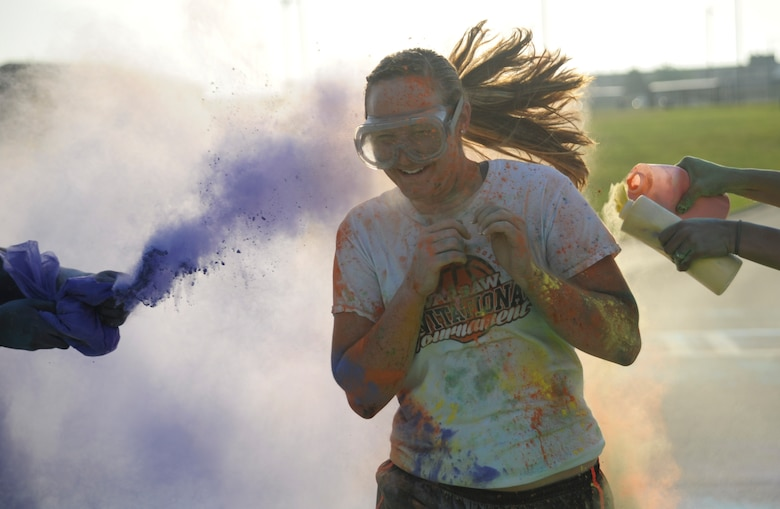 "A participant runs as volunteers throw colored powder on her during the Lesbian, Gay, Bisexual and Transgender (LGBT) Pride Month Rainbow Run 5K at Whiteman Air Force Base, Mo., June 24, 2016. The run promoted the 2016 theme of ""celebration."" (U.S. Air Force photo by Senior Airman Danielle Quilla)"
