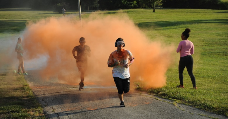 Participants run through a cloud of colored powder during the Lesbian, Gay, Bisexual and Transgender Pride Month Rainbow Run 5K at Whiteman Air Force Base, Mo., June 24, 2016. After the run, the 509th Civil Engineer Squadron fire department washed the powder from the streets. (U.S. Air Force photo by Senior Airman Danielle Quilla)