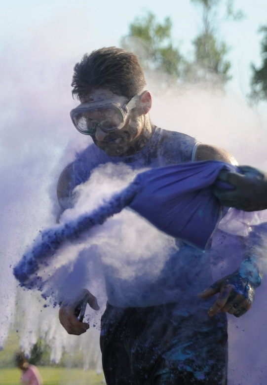 U.S. Air Force Lt. Col. Daniel Murray, a participant of the Lesbian, Gay, Bisexual and Transgender (LGBT) Pride Month Rainbow Run 5K, runs through a cloud of colored powder at Whiteman Air Force Base, Mo., June 24, 2016. The run was one of the LGBT Pride Month events celebrating the great diversity of the American people. (U.S. Air Force photo by Senior Airman Danielle Quilla)