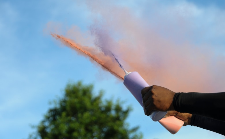 A volunteer sprays colored powder at runners during the Lesbian, Gay, Bisexual and Transgender Pride Month Rainbow Run 5K at Whiteman Air Force Base, Mo., June 24, 2016. A total of 28 volunteers helped setup the event and run the color stations. (U.S. Air Force photo by Senior Airman Danielle Quilla)