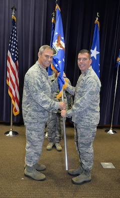 U.S. Air Force Lt. Gen. Mark C. Nowland, 12th Air Force (Air Forces Southern) commander, hands the 557th Weather Wing guidon to U.S. Air Force Col. Steven Dickerson, during a change of command ceremony at the 557th WW Auditorium June 24. Dickerson took command from U.S. Air Force Col. William Carle. (U.S. Air Force photo by Zachary Hada)