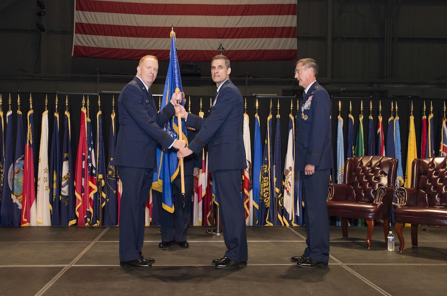In the time-honored military tradition signifying assumption of command, Air Force Research Laboratory Commander Maj. Gen. Robert D. McMurry passes the 711th Human Performance Wing guidon, or unit flag, to Brig. Gen. Mark A. Koeniger. Koeniger assumed command of the wing Jun. 28, 2016, in a ceremony at the National Museum of the United States Air Force. (U.S. Air Force photo/Michelle Gigante)