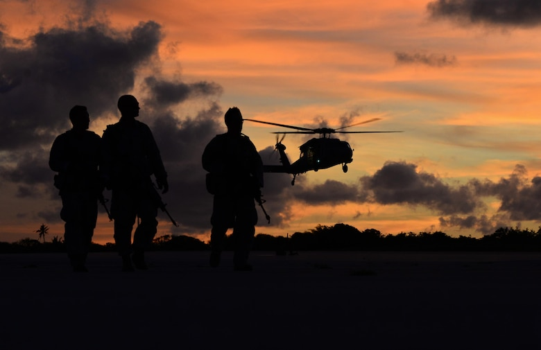 Airmen watch as an MH-60 Seahawk takes off during a jungle training course June 15, 2016, at Andersen Air Force Base, Guam. Conducted by the U.S. Army 25th Infantry Division's Lightning Academy Jungle Operations Training Center from Schofield Barracks, Hawaii, and supported by 736th Security Forces Squadron Commando Warrior cadre, students prepared a simulated patient for medical evacuation. During the course, they also learned survival skills, including land navigation and evasion techniques. (U.S. Air Force photo by Senior Airman Joshua Smoot)