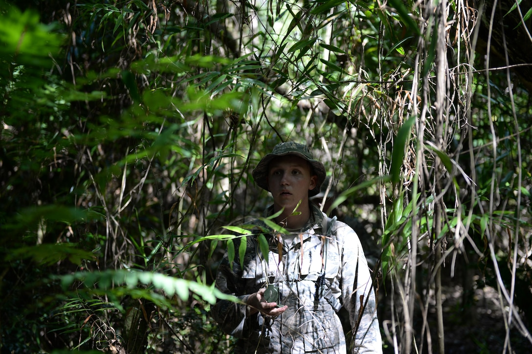 Airman 1st Class Scott Marvin, Jungle Training Operations Course student from the 36th Security Forces Squadron, navigates through the jungle using a compass June 16, 2016, in Barrigada, Guam. The trainees were individually selected from several career fields across the Department of Defense, including Airmen from the 36th Security Forces Squadron, 736th SFS, 554th RED HORSE Squadron, 644th Combat Communications Squadron and infantrymen from the 94th Army Air and Missile Defense Command's Task Force Talon. (U.S. Air Force photo by Tech. Sgt. Richard Ebensberger)