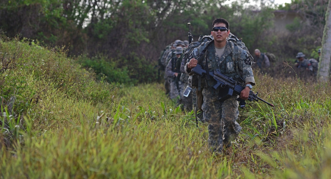 Soldiers and Airmen ruck to an objective point during the Jungle Training Operations Course June 16, 2016, in Barrigada, Guam. Conducted by the U.S. Army 25th Infantry Division's Lightning Academy Jungle Operations Training Center from Schofield Barracks, Hawaii, and supported by 736th Security Forces Squadron Commando Warrior cadre, students prepared a simulated patient for medical evacuation. During the course, they also learned survival skills, including land navigation and evasion techniques. (U.S. Air Force photo by Senior Airman Joshua Smoot)