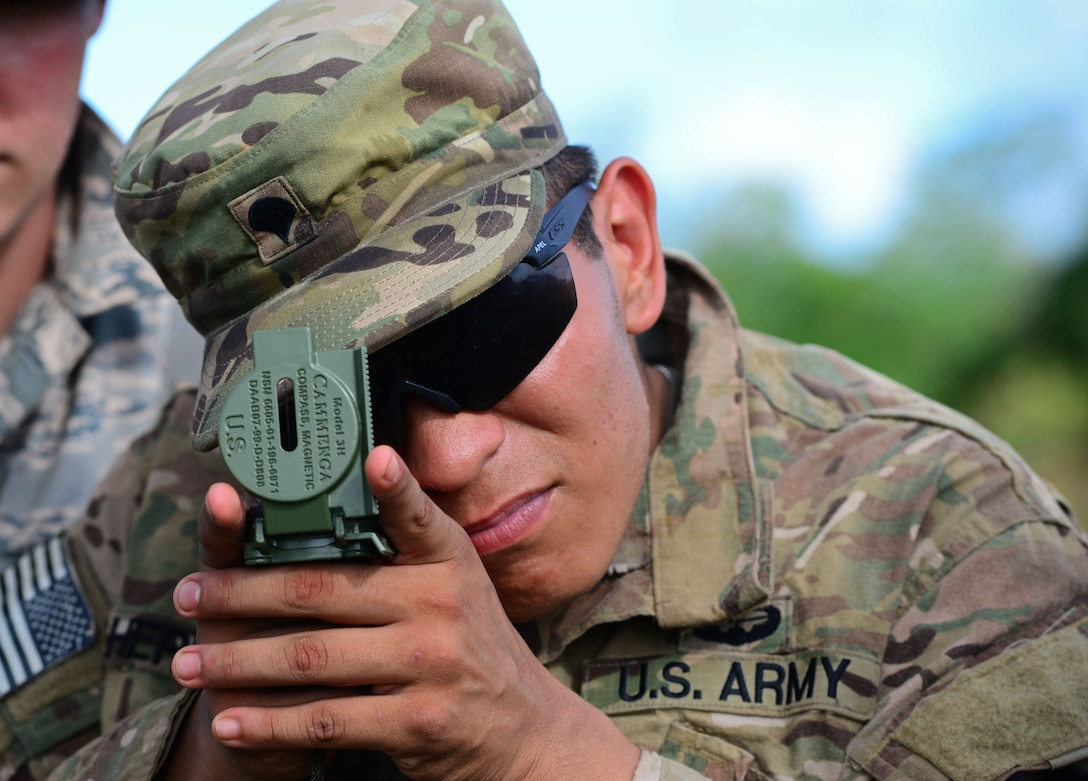 U.S. Army Spc. Matthew Hernandez, Jungle Training Operations Course student from the 94th Army Air and Missile Defense Command's Task Force Talon, takes a compass reading June 16, 2016, at Andersen Air Force Base South, Guam. Conducted by the U.S. Army 25th Infantry Division's Lightning Academy Jungle Operations Training Center from Schofield Barracks, Hawaii, and supported by 736th Security Forces Squadron Commando Warrior cadre, more than 30 Airmen and Soldiers learned the fundamentals of survival skills, including land navigation and evasion techniques. (U.S. Air Force photo by Senior Airman Joshua Smoot)