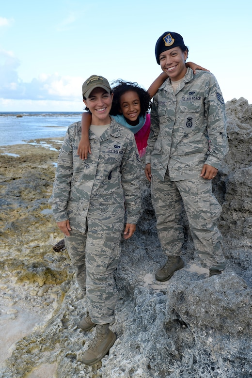 Staff Sgt. Chelsey Coolidge, 736th Security Forces Squadron commando warrior instructor, left, her daughter Akayla, and her wife, Staff Sgt. Tasha Coolidge, 36th SFS unit training manager, stand together June 9, 2016, at Andersen Air Force Base, Guam. The Coolidges have been married for two years after meeting on deployment in Kyrgyzstan in 2013. Together, they enjoy spending time at the beach, hiking and going to Akayla's sporting events. (U.S. Air Force photo by Airman 1st Class Alexa Ann Henderson/Released)