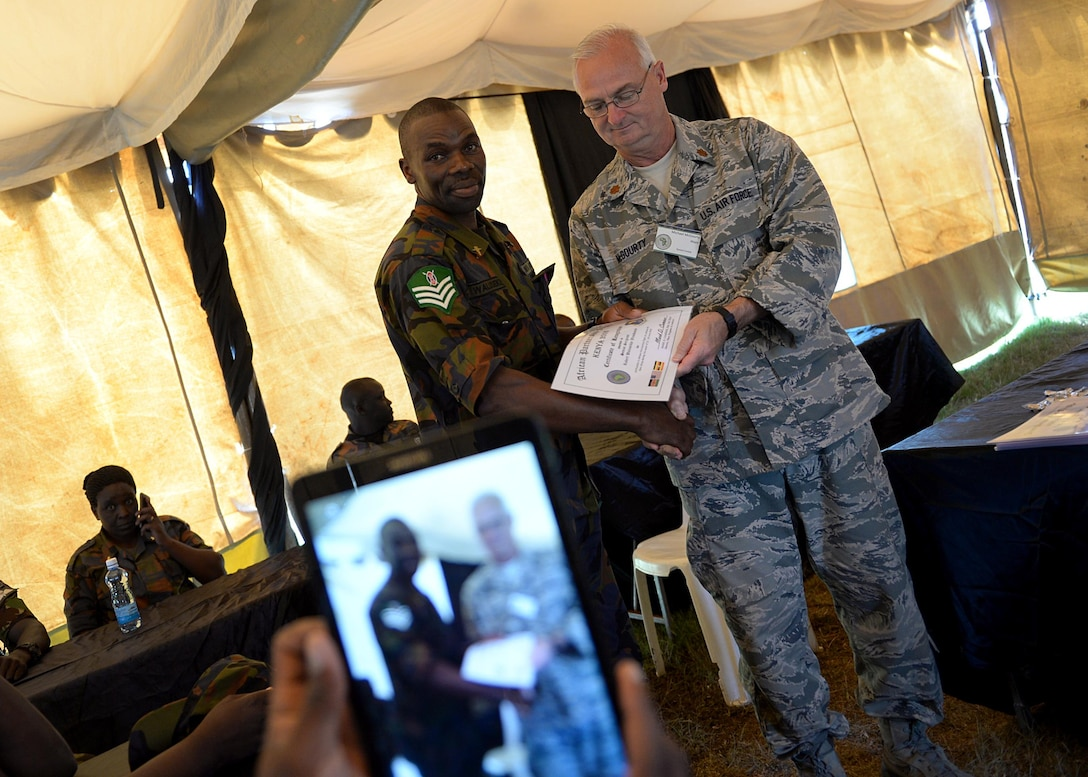 A Kenyan Defense Force member receives a certificate of completion from Maj. Michael McGourty, tactical combat casualty care instructor, 102nd Medical Group, Massachusetts Air National Guard, during African Partnership Flight Kenya June 24, 2016 at Laikipia Air Base, Kenya. More than 50 U.S. Air Force Airmen participated in the first APF in Kenya. The APF is designed for U.S. and African partner nations to work together in a learning environment to help build expertise and professional knowledge and skills. (U.S. Air Force photo by Tech. Sgt. Evelyn Chavez/Released)