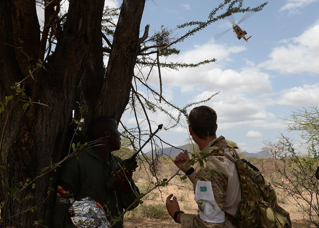 (From left) A Kenyan Defense Force airmen and U.S. Air Force Senior Airman Ian Khun, 82nd Expeditionary Rescue Squadron, survival evasion resistance and escape specialist, watch a helicopter during a hands-on scenario for African Partnership Flight Kenya June 28, 2016 at Archers Post, Kenya.  The APF included a Kenyan-led exercise, Linda Rhino, in which instructors observed the application of what was learned in the classroom and provided feedback. The exercise included multiple personnel recovery scenarios. (U.S. Air Force photo by Tech. Sgt. Evelyn Chavez/Released)