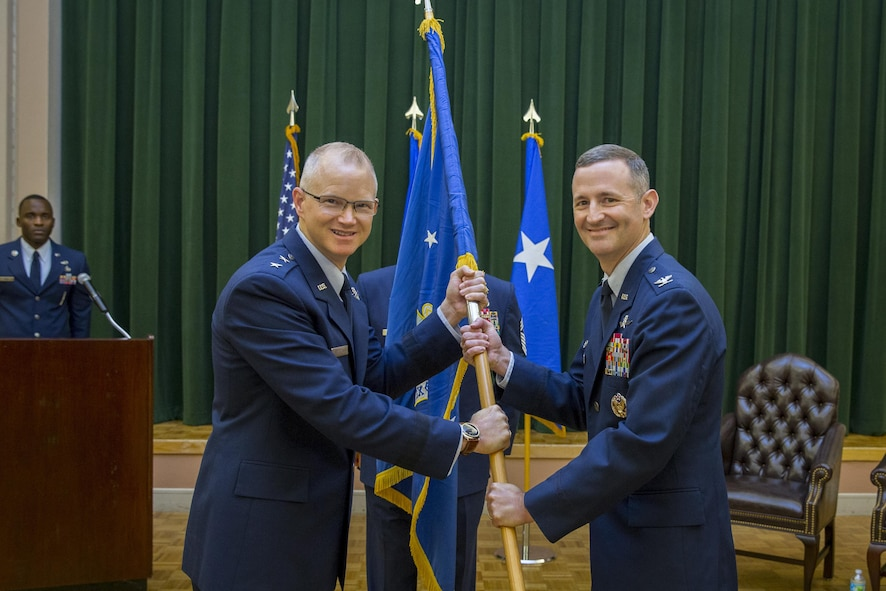 Maj. Gen. Christopher Weggeman, Commander, 24th Air Force, passes the guidon to Col. Bradley Pyburn, Commander, 67th Cyberspace Wing, during the 67CW Change of Command ceremony 28 June.