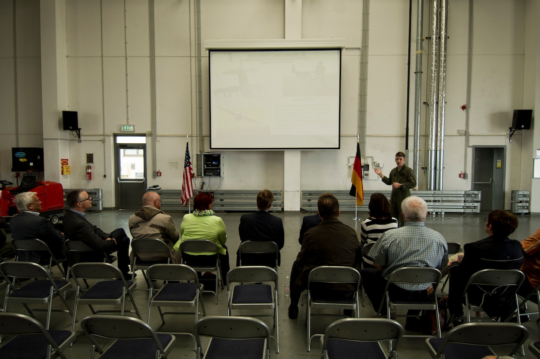 U.S. Air Force Lt. Col. Scott Wilson, 352nd Special Operations Wing director of staff, gives a presentation about CV-22 Osprey tilt-rotor aircaft assigned to his wing during a presentation to local German community leaders on the flightline near the 726th Air Mobility Squadron at Spangdahlem Air Base, Germany, June 28, 2016. The 352nd SOW, currently stationed at Royal Air Force Mildenhall, United Kingdom, will relocate to Spangdahlem as part of the European Infrastructure Consolidation realignment slated over the coming years. (U.S. Air Force Photo by Staff Sgt. Joe W. McFadden/Released)