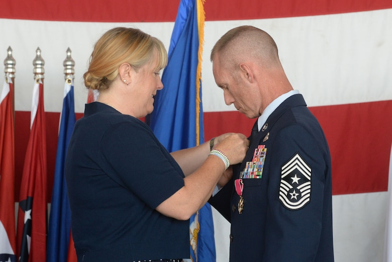 Chief Master Sgt. Geoff Weimer, accepts the retirement pin from his wife, LeAnn, at his retirement ceremony at Minot Air Force Base, N.D., June 24, 2016. Weimer retired after 29 years of service and recently served as the command chief of the 5th Bomb Wing. (U.S. Air Force photo/Airman 1st Class Jessica Weissman)