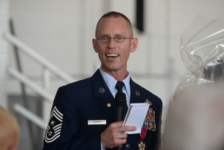 Chief Master Sgt. Geoff Weimer smiles at the crowd during his retirement ceremony at Minot Air Force Base, N.D., June 24, 2016. Weimer retired after 29 years of service and recently served as the command chief of the 5th Bomb Wing. (U.S. Air Force photo/Airman 1st Class Jessica Weissman)