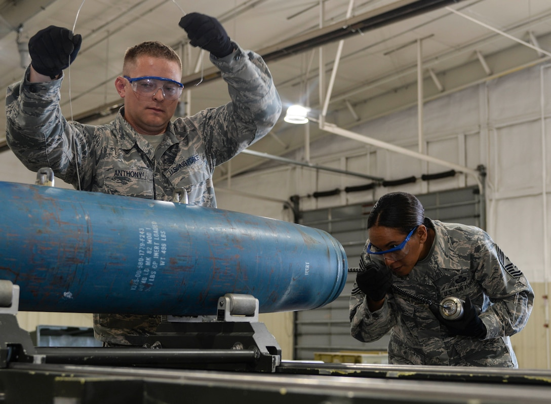 Senior Airman Justin Anthony, 28th Munitions Squadron conventional maintenance crew chief, left, assists Chief Master Sgt. Sonia Lee, 28th Bomb Wing command chief, in loading an FM-152 fuse into an inert GBU-38 v1 during an immersion tour at Ellsworth Air Force Base, S.D., June 27, 2016. Ellsworth's conventional maintenance crews take an average of 25 minutes to build the 500-pound munition. (U.S. Air Force photo by Airman 1st Class Sadie Colbert/Released)