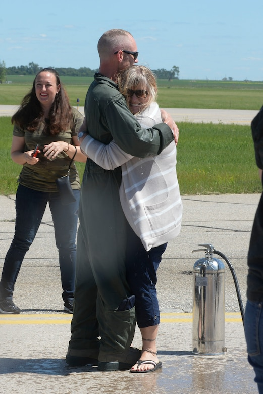 """Chief Master Sgt. Geoff Weimer hugs his wife LeAnne after celebration of his """"fini-flight"""" at Minot Air Force Base, N.D., June 23, 2016. The """"fini-flight"""" is the final flight taken by an aircrew member at his current assignment. (U.S. Air Force photo/Airman 1st Class Jessica Weissman)"""