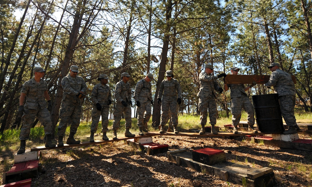 Airmen From the 28th Civil Engineer Squadron participate in a leadership reaction course at the South Dakota National Guard West Camp Rapid training facility, Rapid City, S.D., June 17, 2016. The purpose of the LRC was to develop teamwork building and communication skills. (U.S. Air Force photo by Airman 1st Class Denise M. Nevins/Released)